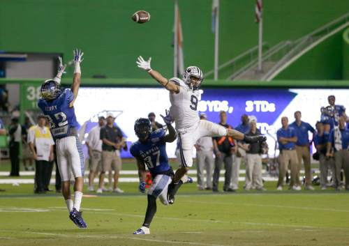 The Ball goes past BYU wide receiver Jordan Leslie (9) into the hands of Memphis defensive back DaShaughn Terry (32) for an interception to end the inaugural Miami Beach Bowl NCAA college football game, Monday, Dec. 22, 2014 in Miami. Memphis won 55-48 in two overtimes. (AP Photo/Wilfredo Lee)