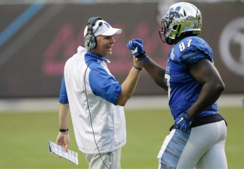 Memphis head coach Justin Fuente congratulates defensive lineman Martin Ifedi (97) after a play during the second half of the in the inaugural Miami Beach Bowl football game against Brigham Young, Monday, Dec. 22, 2014 in Miami. Memphis defeated Brigham Young 55-48 in double overtime. (AP Photo/Wilfredo Lee)