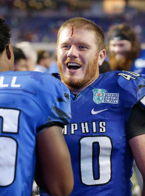 Memphis tight end Alan Cross (40) bleeds from the head as he celebrates with teammates after players scuffled on the field after Memphis defeated Brigham Young 55-48 in double overtime during the inaugural Miami Beach Bowl football game, Monday, Dec. 22, 2014 in Miami. (AP Photo/Wilfredo Lee)