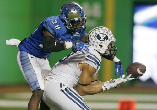 BYU wide receiver Jordan Leslie, right, is unable to hang on to a pass as Memphis defensive back Andrew Gaines (28) reaches for the ball during the second half of the in the inaugural Miami Beach Bowl NCAA college football game, Monday, Dec. 22, 2014, in Miami. Memphis defeated BYU 55-48 in two overtimes. (AP Photo/Wilfredo Lee)