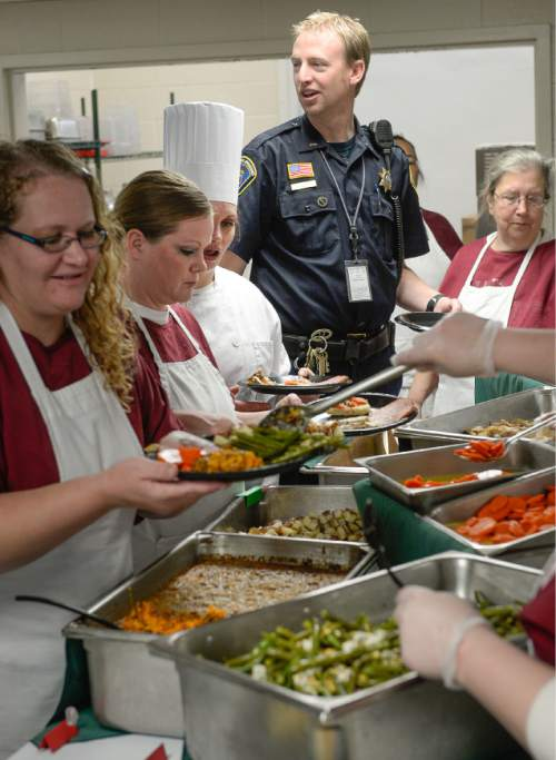 Francisco Kjolseth  |  The Salt Lake Tribune Officer Ericson Smith towers over the female inmates as they prepare a holiday luncheon on Friday, Dec 5, 2014.