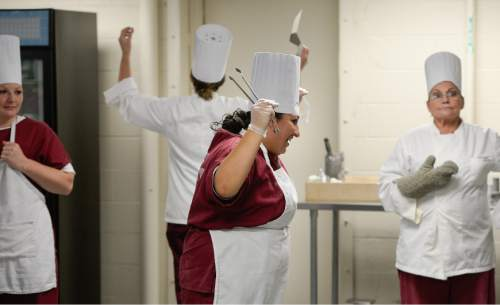 Francisco Kjolseth  |  The Salt Lake Tribune A moment of levity: Tina Deluna, center, spins and sings as food comes together for a Holiday Luncheon. For the women participating in the prison's culinary arts program, it means a break from the regular bad prison food and a chance to each fresh fruits and vegetables.