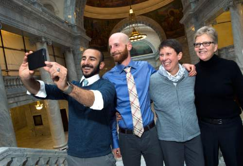 Scott Sommerdorf   |  The Salt Lake Tribune Moudi Sbeity, left, takes a photo of his husband Derek Kitchen, and Kody Partridge and Laurie Wood, far right, at the Utah State Capitol, Sunday, Dec. 21, 2014.