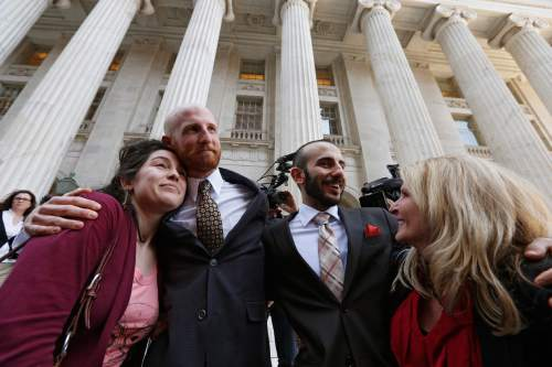 Plaintiff and gay rights activist Derek Kitchen, center left, hugs his cousin Amelia Davis, left, as Derek's partner Moudi Sbeity hugs his mother Joni Jensen, after leaving court following a hearing at the U.S. Circuit Court of Appeals in Denver, Thursday, April 10, 2014. The court is to decide if it agrees with a federal judge in Utah who in mid-December overturned a 2004 voter-passed gay marriage ban, saying it violates gay and lesbian couples' rights to due process and equal protection under the 14th Amendment. (AP Photo/Brennan Linsley)