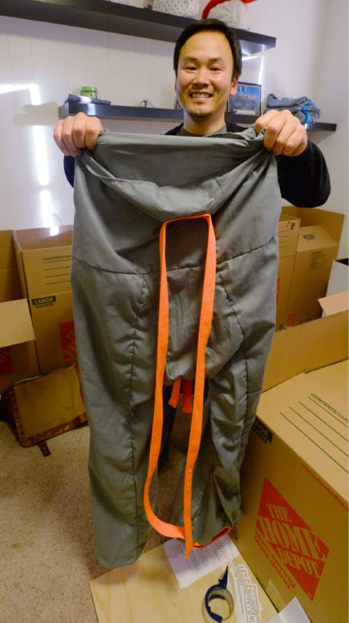 "Steve Griffin  |  The Salt Lake Tribune  University of Utah student Garred Lentz holds up a pair of ""Sakpants""  which are like footie sweatpants for grownups and kids. Lentz teamed up with fellow student Brayden Iwasaki  to create the pants and they have received about 1,000 orders for their first run of the pants. They are photographed here in their makeshift warehouse at Brayden Iwasaki's house in Holladay, Utah Wednesday, December 10, 2014."