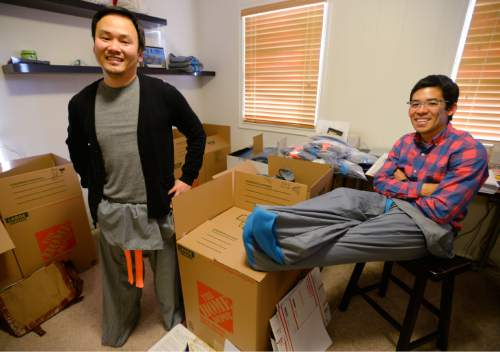 "Steve Griffin  |  The Salt Lake Tribune  University of Utah students Garred Lentz and Brayden Iwasaki wear their ""Sakpants""  which are like footie sweatpants for grownups and kids. They have received about 1,000 orders for their first run of the pants. They are photographed here in their makeshift warehouse at Brayden Iwasaki's house in Holladay, Utah Wednesday, December 10, 2014."