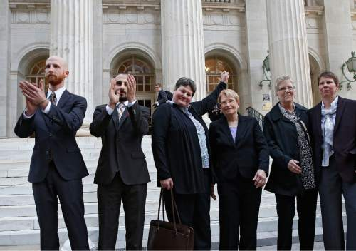 Brennan Linsley  |  The Associated Press Plaintiffs challenging Utah's gay marriage ban, from left, Derek Kitchen, his partner Moudi Sbeity, Kate Call, her partner Karen Archer, Laurie Wood and her partner Kody Partridge stand together after leaving court following a hearing at the U.S. Circuit Court of Appeals in Denver in April. The court is to decide if it agrees with a federal judge in Utah who in mid-December overturned a 2004 voter-passed gay marriage ban, saying it violates gay and lesbian couples' rights to due process and equal protection under the 14th Amendment.