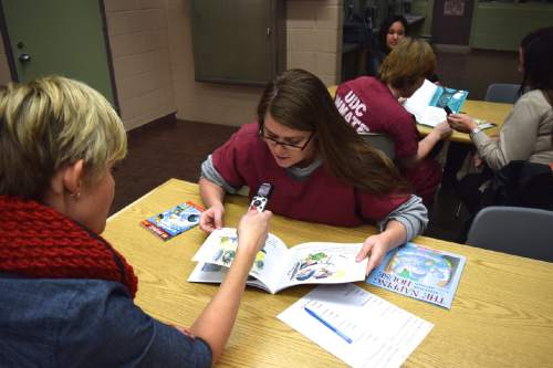 (Brooke Adams, Utah Department of Corrections) Volunteer Kristin Kmetzsch reads with inmate Maria King as part of the Utah State Prison's Bedtime Stories Program.