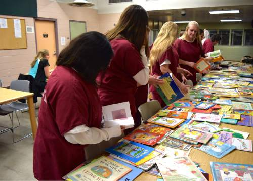 (Brooke Adams, Utah Department of Corrections) Women look through books available as part of the Utah State Prison's Bedtime Stories Program.