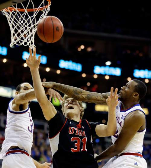 Utah's Dallin Bachynski (31) is fouled as he shoots under pressure from Kansas' Perry Ellis, left, and Cliff Alexander, right, during the second half of an NCAA college basketball game Saturday, Dec. 13, 2014, in Kansas City, Mo. Kansas won 63-60.  (AP Photo/Charlie Riedel)