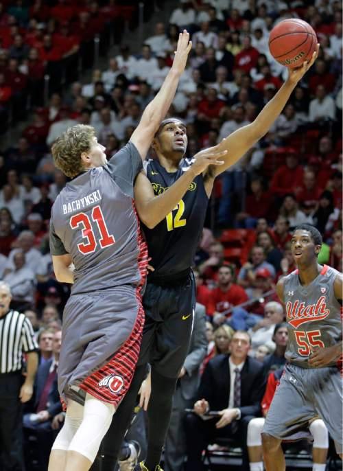 Wichita State forward Darius Carter (12) shoots as Utah center Dallin Bachynski (31) defends in the second half during an NCAA college basketball game Wednesday, Dec. 3, 2014, in Salt Lake City. (AP Photo/Rick Bowmer)