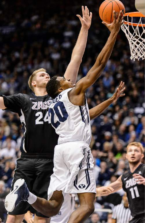 Trent Nelson  |  The Salt Lake Tribune Brigham Young Cougars guard Anson Winder (20) puts up a shot ahead of Gonzaga Bulldogs center Przemek Karnowski (24) as BYU hosts Gonzaga, men's college basketball at the Marriott Center in Provo, Saturday December 27, 2014.