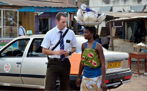 Mike Stack  |  special to The Salt Lake Tribune  LDS missionary Thomas Fornaro attempting to get address from a local woman while street contacting in Accra, Ghana.  03/05/2014