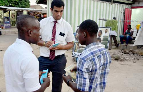 Mike Stack  |  special to The Salt Lake Tribune  Elder Isaac Nyarko(Left) and Elder Aumua(Right) attempting to make an appointment to teach during a typical LDS missionary street display in Accra, Ghana. 3/5/2014