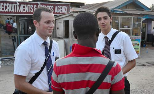 Mike Stack  |  special to The Salt Lake Tribune  LDS missionaries Thomas Fornaro (left) and Tyler Valdez(right) talk to a local Ghanaian while street contacting in Accra, Ghana.  03/05/2014