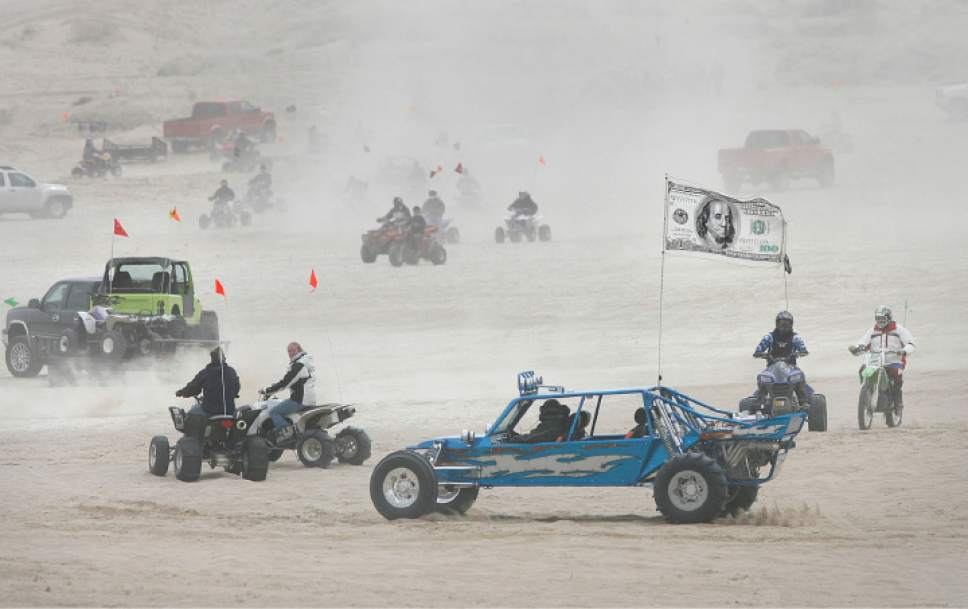 "Scott Sommerdorf  |   Tribune file photo  A ""sand rail"" dune buggy with a $100 bill flag drives among other off-road enthusiasts at Little Sahara Recreation Area."