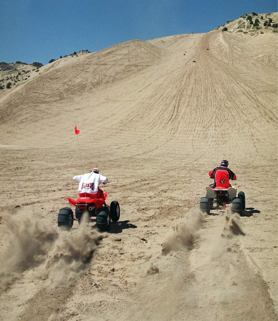 (Tribune file photo) Roger Berg, of South Jordan, left,and Jared Garn of Riverton, right, dig out on their ATV's at the bottom of Big Sand Mountain to get enough momentum to carry them to the top.