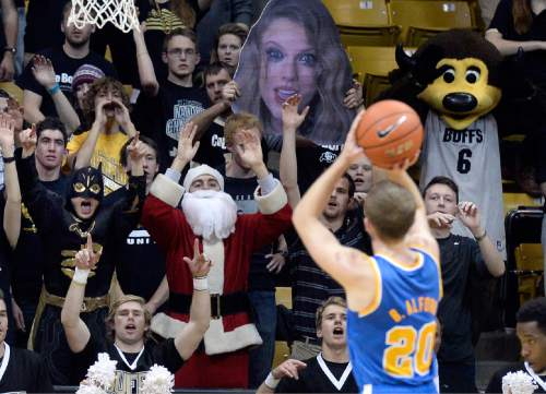 Colorado fans including two people dressed as Santa Claus and Batman heckle UCLA's Bryce Alford as he shoots a free throw during the second half of an NCAA college basketball game Friday, Jan 2, 2015, in Boulder, Colo. (AP Photo/The Daily Camera, Jeremy Papasso)