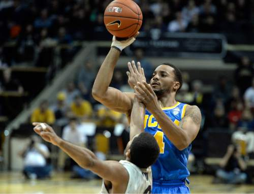 UCLA's Norman Powell takes a shot over Xavier Talton during the second-half of an NCAA basketball game against Colorado on Friday, Jan 2, 2015, in Boulder, Colo. (AP Photo/The Daily Camera, Jermy Papasso)