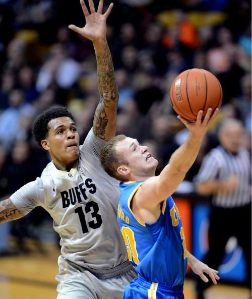UCLA's Bryce Alford drives past Colorado's Dustin Thomas during the first half of an NCAA college basketball game Friday, Jan. 2, 2015, in Boulder, Colo. (AP Photo/The Daily Camera, Cliff Grassmick)