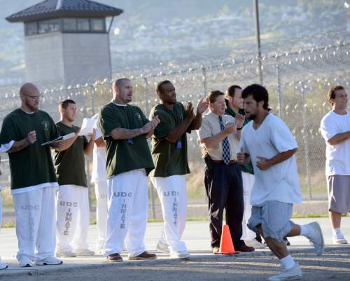 Al Hartmann  |  The Salt Lake Tribune Inmates and prison staff cheer on and time 43 male inmates in the Con-Quest substance abuse program run in the first 5K race at the Utah State Prison. A new bill would allow the prison to stay in Draper.