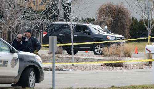 Francisco Kjolseth  |  The Salt Lake Tribune A black SUV, still with the unseen body of a suspect shot and killed in the front seat by a West Valley police officer attempting a possible narcotics arrest sits in the Cranberry Hill neighborhood in Draper on Wednesday morning, Jan. 14, 2015. A West Valley police officer on his way to work who asked for back up from Draper police shot and killed the suspect when he brandished a knife during the struggle to arrest him.