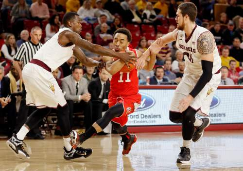 Utah's Brandon Taylor (11) fights through Arizona State's, right, and Gerry Blakes, left, during the first half of an NCAA college basketball game, Thursday, Jan. 15, 2015, in Tempe, Ariz. (AP Photo/Matt York)