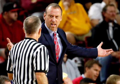 Utah head coach Larry Krystkowiak, right, argues with the referee during the first half of an NCAA college basketball game against Arizona State, Thursday, Jan. 15, 2015, in Tempe, Ariz. (AP Photo/Matt York)