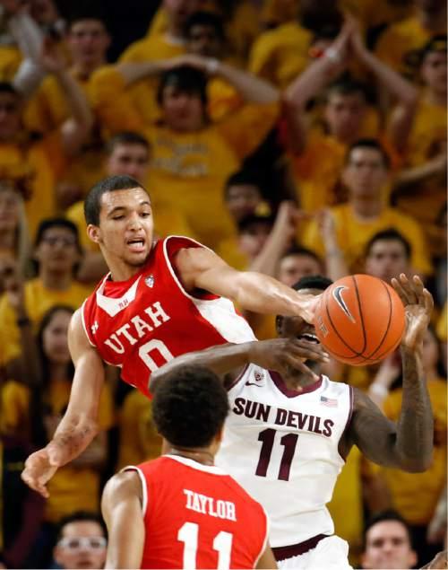 Utah's Brekkot Chapman (0) knocks the ball away from Arizona State' Savon Goodman (11) during the first half of an NCAA college basketball game, Thursday, Jan. 15, 2015, in Tempe, Ariz. (AP Photo/Matt York)