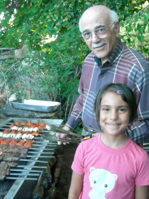 Courtesy | Jennifer Melcomian  Mel Melcomian, owner of  Casa Melinda, cooking with his granddaughter, Julia.