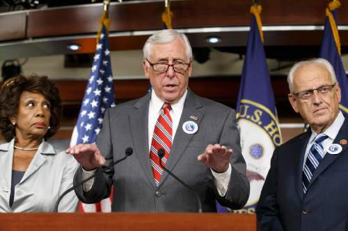 House Minority Whip Steny Hoyer of Md., joined by Rep. Maxine Waters, D-Calif., left, and Rep. Kerry Bentivolio, R-Mich., criticizes the efforts of Republicans to muscle legislation through the House authorizing an election-year lawsuit against President Barack Obama that accuses him of exceeding his powers in enforcing his health care law, Wednesday, July 30, 2014, during a news conference on Capitol Hill in Washington. Democrats have branded the effort a political charade aimed at stirring up Republican voters for the fall congressional elections. They say it's also an effort by top Republicans to mollify conservatives who want Obama to be impeached -- something House Speaker John Boehner of Ohio, said Tuesday he has no plans to do.  (AP Photo/J. Scott Applewhite)