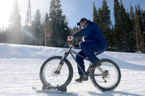 "Al Hartmann  |  The Salt Lake Tribune L. Jason Loveland of Lovelands Cycle in Brigham City demos a ""Bike Board"" at the Winter Market Outdoor Retailers at Solitude Mountain Resort for the All Mountain Demo Tuesday January 20, 2015. It's a short ski with brackets that attach to a fat-tire bike allowing it to be ridden in snow. The demo day gives retailers the opportunity to test gear in the environment it was made for to make informed buying decisions."