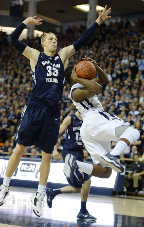 Steve Griffin  |  The Salt Lake Tribune  Brigham Young Cougars forward Nate Austin (33) leaps above Utah State Aggies guard Darius Perkins (2) as Perkins tries to get a shot off during second half action in the BYU versus USU men's basketball game in Logan, Tuesday, December 2, 2014.
