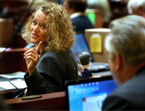 Scott Sommerdorf  |  Tribune file photo Then-Rep. Neil A. Hansen (right) D-Ogden, taunts fellow Rep. Jackie Biskupski D-Salt Lake City, with his bobble-head doll of Mitt Romney as the House was beginning its work in a 2008 special session of the Legislature.