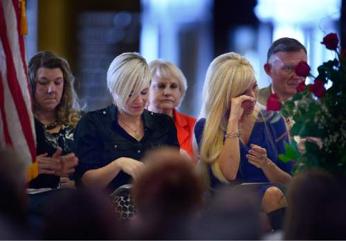 Scott Sommerdorf   |  The Salt Lake Tribune Desirae Payne, sister of Draper City Sgt. Derek Johnson, left, listens as Nanette Wride wipes away a tear during Utah's Salute to Law and Order held in the Hall of Governors at the State Capitol, Thursday, January 29, 2015. Wride is the wife of Utah County Sgt. Cory Wride. At the far left is Shawna Harris, wife of Kane County Deputy Brian Harris.