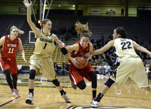 Utah's Danielle Rodriguez drives past Colorado defenders, including Lexy Kresl, left, and Haley Smith during the first half of an NCAA college basketball game Wednesday, Jan. 14, 2015, in Boulder, Colo. (AP Photo/Daily Camera, Jeremy Papasso)