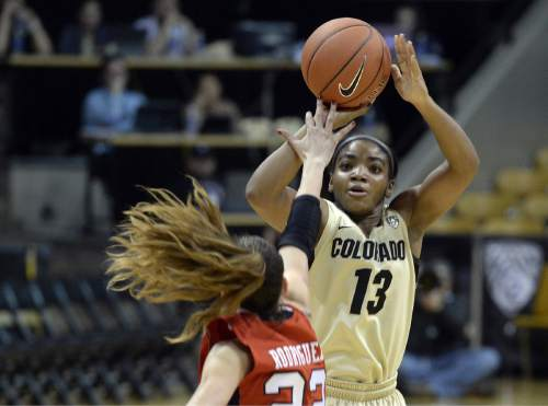 Colorado's Brecca Thomas sinks a 3-pointer over Utah's Danielle Rodriguez during the first half of an NCAA college basketball game Wednesday, Jan. 14, 2015, in Boulder, Colo. (AP Photo/Daily Camera, Jeremy Papasso)