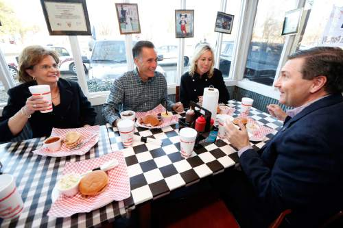 Former GOP presidential candidate Mitt Romney, second from left, former Mississippi Republican Lt. Gov. Amy Tuck, left, Megan Mullen, wife of Mississippi State football coach Dan Mullen and Dan Mullen, right, talk as they have dinner at Little Dooey, a barbecue restaurant in Starkville, Miss., Wednesday, Jan. 28, 2015. Romney hasn't officially declared himself a presidential candidate again, but the 2012 Republican nominee looked and sounded like one during the stop in Mississippi. (AP Photo/Rogelio V. Solis)