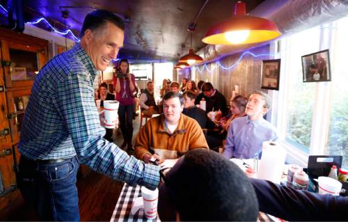Former GOP presidential candidate Mitt Romney visits with diners at Little Dooey, a barbecue restaurant in Starkville, Miss., Wednesday, Jan. 28, 2015. Romney hasn't officially declared himself a presidential candidate again, but the 2012 Republican nominee looked and sounded like one during the stop in Mississippi. (AP Photo/Rogelio V. Solis)