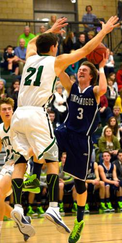 Leah Hogsten  |  The Salt Lake Tribune Timpanogos' Josh Alphin tries to drive to the net through Olympus' Jake Lindsey. Timpanogos High School's boys basketball team defeated Olympus High School 49-42, Tuesday, January 20, 2015 at Olympus.