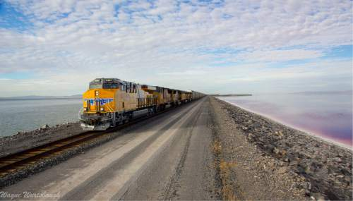 Wayne Wurtsbaugh     Utah State University  A Union Pacific train traverses the rock causeway crossing the north end of Utah's Great Salt Lake. Since 1959 this causeway has isolated the hyper-saline North Arm, the reddish water on the right, from the rest of the lake to the south. Utah and federal regulators are now weighing the railroad's plan to construct a 150-foot breach and bridge that would allow water to travel back and forth. Without such mixing, the lake's overseers fear the South Arm could experience swings in its salt load to the detriment of industries and tiny organisms that depend on the lake.