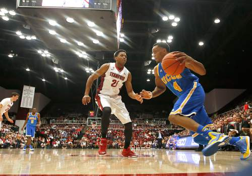 UCLA guard Norman Powell (4) drives past Stanford forward Anthony Brown (21) during the first half of an NCAA college basketball game Thursday, Feb. 5, 2015, in Stanford, Calif. (AP Photo/Tony Avelar)