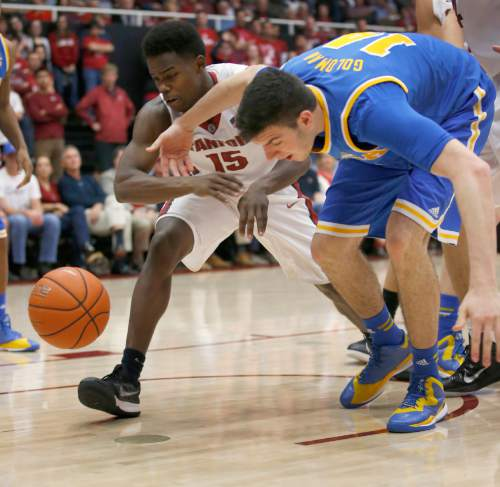 UCLA forward Gyorgy Goloman (14) and Stanford guard Marcus Allen (15) vie for a loose ball during the second half of an NCAA college basketball game Thursday, Feb. 5, 2015, in Stanford, Calif. UCLA won 69-67. (AP Photo/Tony Avelar)