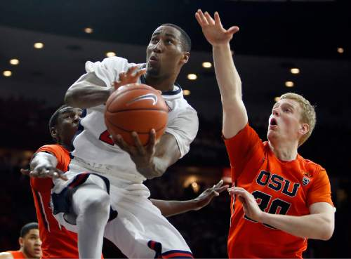 Arizona forward Rondae Hollis-Jefferson, middle, drives between Oregon State's Daniel Gomis, left, and Olaf Schaftenaar during the second half of an NCAA college basketball game, Friday, Jan. 30, 2015, in Tucson, Ariz. (AP Photo/Rick Scuteri)