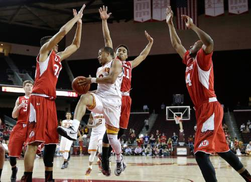 Southern California's Chass Bryan, center, passes the ball as he is defended by Utah's Kyle Kuzma, left, Brandon Taylor and Dakarai Tucker, right, during the second half of an NCAA college basketball game, Sunday, Feb. 1, 2015, in Los Angeles. Utah won 67-39. (AP Photo/Jae C. Hong)