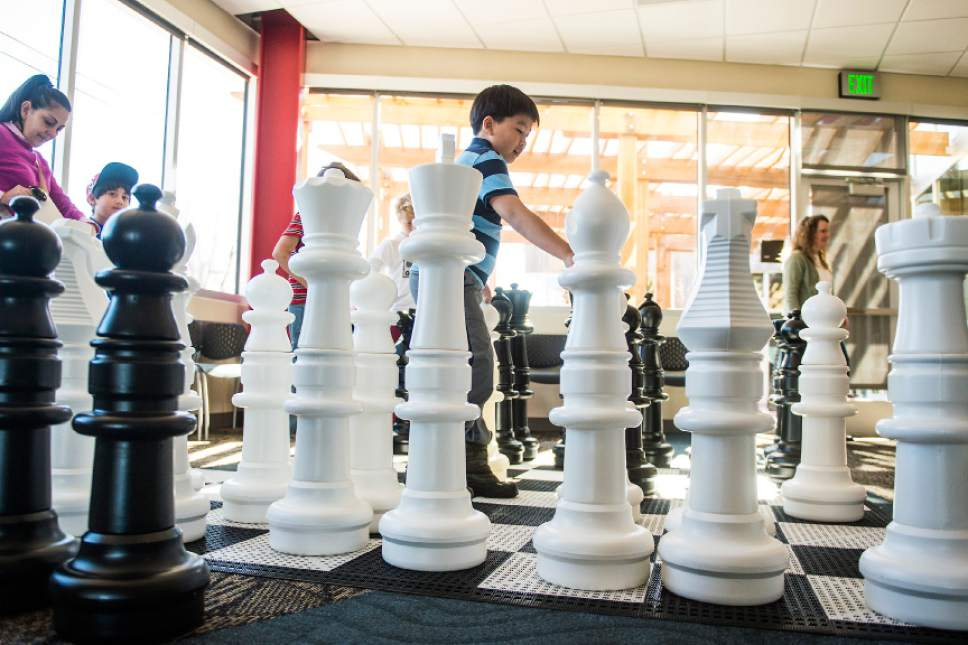 Chris Detrick  |  The Salt Lake Tribune Kids play chess during the grand opening of the Glendale Branch library on Saturday. The branch features nearly 20,000 square feet of space, making it the largest City Library branch, and offers 40,000 items for circulation. The branch also includes a large meeting facility, a designated teen space, and a floor plan that offers open views across the building.