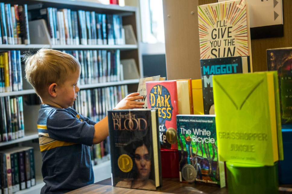 Chris Detrick  |  The Salt Lake Tribune Peirce Frandsen, 2, helps his dad Jordan Frandsen (not pictured) pick out books during the grand opening of the Glendale Branch library Saturday February 7, 2015.   The branch features nearly 20,000 square feet of space, making it the largest City Library branch, and offers 40,000 items for circulation. The branch also includes a large meeting facility, a designated teen space, and a floor plan that offers open views across the building.
