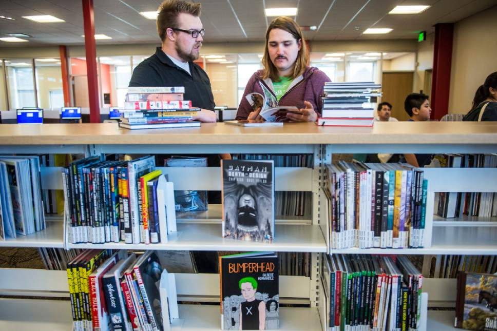 Chris Detrick  |  The Salt Lake Tribune Eric Evans, of Salt Lake City, and Spencer Holt, of Rose Park, look at comic and cook books during the grand opening of the Glendale Branch library Saturday February 7, 2015.   The branch features nearly 20,000 square feet of space, making it the largest City Library branch, and offers 40,000 items for circulation. The branch also includes a large meeting facility, a designated teen space, and a floor plan that offers open views across the building.