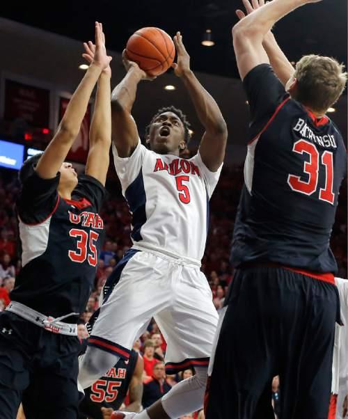 Arizona forward Stanley Johnson (5) shoots between Utah forward Kyle Kuzma (35) and Dallin Bachynski (31) during the second half of an NCAA college basketball game, Saturday, Jan. 17, 2015, in Tucson, Ariz. (AP Photo/Rick Scuteri)
