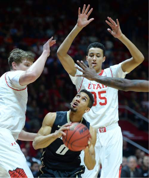 Steve Griffin  |  The Salt Lake Tribune   Colorado Buffaloes guard Askia Booker (0) has no where to go as he gets trapped under the basket by Utah Utes center Dallin Bachynski (31) and Utah Utes forward Kyle Kuzma (35) during second half action in the Utah versus Colorado men's basketball game at the Huntsman Center in Salt Lake City, Wednesday, January 7, 2015.